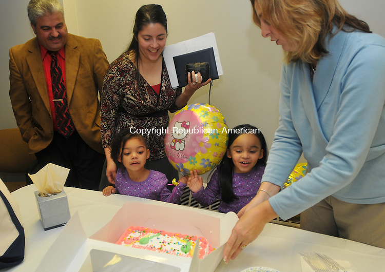 WATERBURY, CT- 20 November 2009 - 112009IP04- Kathy DePasquale of Adoption Resource Exchange of the Department of Children and Families, presents a cake to (from right) Serenity, 3, Felisha, 3, and Brenda and David Torres after the couple received adoption papers for the children at Waterbury Probate Court on Friday.  <br /> Irena Pastorello Republican-American