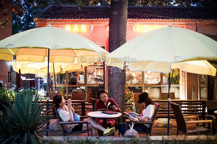 Three chinese girls relax in a bar in 798 Art District in Beijing, China, July 19, 2014. <br /> <br /> 798 Art District (Chinese: 798艺术区; pinyin: 798 Yìshùqū), or Dashanzi Art District, is a 50-year old decommissioned military factory buildings with unique architectural style. Located in Chaoyang District of Beijing, that houses a thriving artistic community. Since the beginning of 2000, 798 has become a centre for art galleries, artists's ateliers and contemporary arts exhibitions. The buildings are within alleys number 2 and 4 on Jiǔxiānqiáo Lù (酒仙桥路), south of the Dàshānziqiáo flyover (大山子桥). <br /> <br /> © Giorgio Perottino