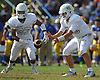 Oceanside quarterback No. 18 Vincent Guarino takes a snap as running back No. 33 Brandy Diaz blocks for him during a Nassau County Conference I varsity football game against host East Meadow High School on Saturday, September 26, 2015. Oceanside won by a score of 14-7.<br /> <br /> James Escher