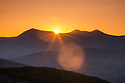 The sun escapes the horizon at the beginning of another day in New Hampshire's White Mountains.s