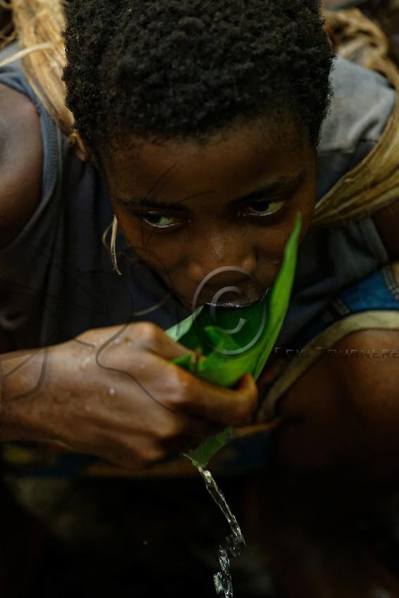 """In the forest, a woman drinks water from a stream with the aid of a """"Goutou"""" leaf.///En forêt, une femme boit de l'eau d'une rivière à l'aide d'une feuille «Goutou» system."""