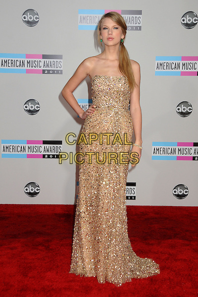 Taylor Swift.2011 American Music Awards - Arrivals held at Nokia Theatre LA Live, Los Angeles, California, USA..November 20th, 2011.ama amas ama's full length dress maxi  gold beige embellished jewel encrusted bead beaded dress ponytail hand on hip.CAP/ADM/BP.©Byron Purvis/AdMedia/Capital Pictures.