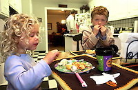 Oct 21, 2004 - Pleasanton, CA, USA - 6:33 PM: Lena, 3, and brother Aleks Twarowski, 6, have dinner  in Pleasanton, Calif., Thursday Oct. 21, 2004 complete with Halloween place mats . Their father Joe is in the background putting his dinner together just after arriving home from work..(Credit Image: © Alan Greth)