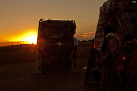 Sunset at Cadillac Ranch, a  public art installation and sculpture in Amarillo, Texas, U.S. It was created in 1974 by Chip Lord, Hudson Marquez and Doug Michels, who were a part of the art group Ant Farm, and it consists of what were (when originally installed during 1974) either older running used or junk Cadillac automobiles, representing a number of evolutions of the car line (most notably the birth and death of the defining feature of early Cadillacs; the tail fin) from 1949 to 1963, half-buried nose-first in the ground, at an angle corresponding to that of the Great Pyramid of Giza in Egypt.