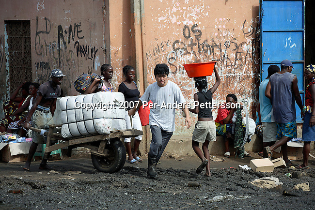 LUANDA, ANGOLA MARCH 31: A Chinese businessman pulls a cart with imported Chinese good with his Angolan workers on March 31, 2007 at the Chinese market in Luanda. Luanda is full of newly arrived Chinese who do business in many different fields. Tens of thousands of Chinese has come to Africa the last years to work in infrastructure projects and businesses. Chinese companies are often the lowest bidders for contracts, pricing out the more expensive European companies. The Chinese people often live where they work and rarely interact with the local population. Most Chinese don't speak English and they are mostly staying in the compounds cooking their Chinese food. .(Photo by Per-Anders Pettersson)....