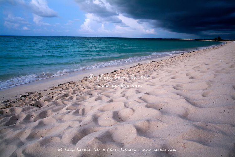 White sand beach and beautiful waters under an ominous stormy sky at Cayo Santa-Maria, Cuba.