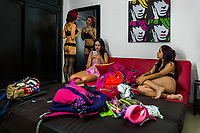 Colombian cam models put on their lingerie and make-ups before performing live shows, broadcasted online from a webcam model studio in Medellín, Colombia, 4 March 2016. With the traditional adoration of female beauty in Colombia, together with rapidly developing telecommunications technologies, the millennial generations of Colombian girls have turned the city of Medellín during the past few years into a one of the world centers of webcam modelling, a booming interractive sex industry. Thousands of young women stream everyday via websites that allow the global viewers to personally interract with a model and to pay them for sexually related acts. Although the core of the show is always based on stripping, the crucial part of a cam girl's success is communication. Cam models who have the ability of light conversation, flirting and entertaining the viewer earn thousands of dollars a month and have moved far beyond the borders of sexuality. Sharing their whole lives in a constant interaction with their online clients, they have built regular relationships in the cyberspace.