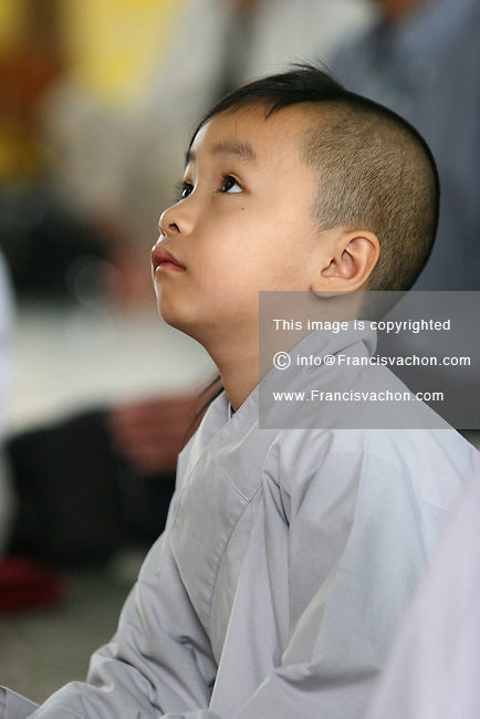 A six years old kid listens to Bharte (venerable) Rahula talking during the Sanghadana service, a traditional way of showing respects to monks for preserving the teaching of the Buddha, at Linh Son Temple at 706 Goyeau Street Saturday July 22, 2006. A public talk about Vipassana Meditation was given at the temple for people interesting to learn about the technic.