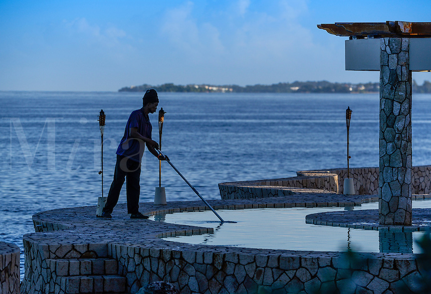 Man cleans resort oceanfront pool, Negril, Jamaica