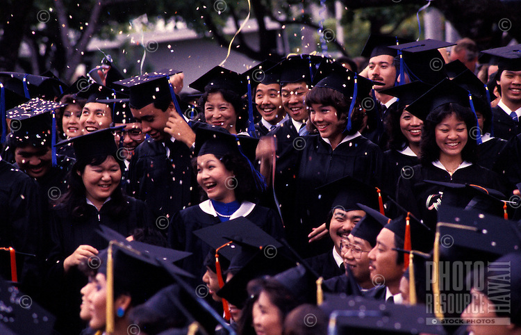 Group celebrating at their graduation ceremony with confetti in the air, University of Hawaii