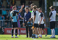 Garry Thompson of Wycombe Wanderers talks with Wycombe Wanderers Manager Gareth Ainsworth and his staff during a break in play during the Sky Bet League 2 match between Wycombe Wanderers and Plymouth Argyle at Adams Park, High Wycombe, England on 12 September 2015. Photo by Andy Rowland.