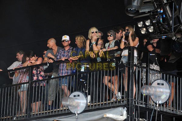 LUKE WORRALL & KELLY OSBOURNE .Watching a performance during Glastonbury Festival 2010, Worthy Farm, Glastonbury, England, UK, .June 26th 2010..Glasto music concert gig audience full length sunglasses couple backstage black vest .CAP/WIZ.© Wizard/Capital Pictures.