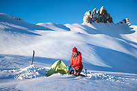 A woman stands next to her tent during a winter snow camping trip, with the Löbhorner in the background, above Lauterbrunnen, Switzerland