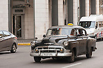 Havana, Cuba; a black, classic 1953 Chevy car serving as a taxi, driving down the street in Havana