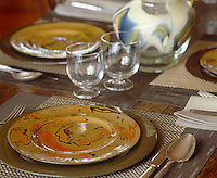 The table is laid with a set of patterend earthenware plates and simple short-stemmed wine glasses