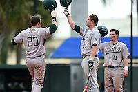 Slippery Rock Adam Urbania (20) is congratulated at home by Alex Bell (14) and Jordan Faretta (11) after hitting a home run during a game against the University of the Sciences Devils on March 6, 2015 at Jack Russell Field in Clearwater, Florida.  Slippery Rock defeated University of the Sciences 6-3.  (Mike Janes/Four Seam Images)
