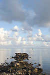 Moorea, French Polynesia; sunrise view of an abandoned, broken down pier with channel markers off in the distance , Copyright © Matthew Meier, matthewmeierphoto.com All Rights Reserved
