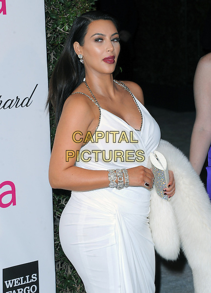 Kim Kardashian.The 21st Annual Elton John AIDS Foundation Academy Awards Viewing Party held at The City of West Hollywood Park in West Hollywood, California, USA..February 24th, 2013.oscars full length white sleeveless dress carrying fur pregnant diamond bracelet halterneck clutch bag mouth open funny red lipstick .CAP/DVS.©DVS/Capital Pictures.
