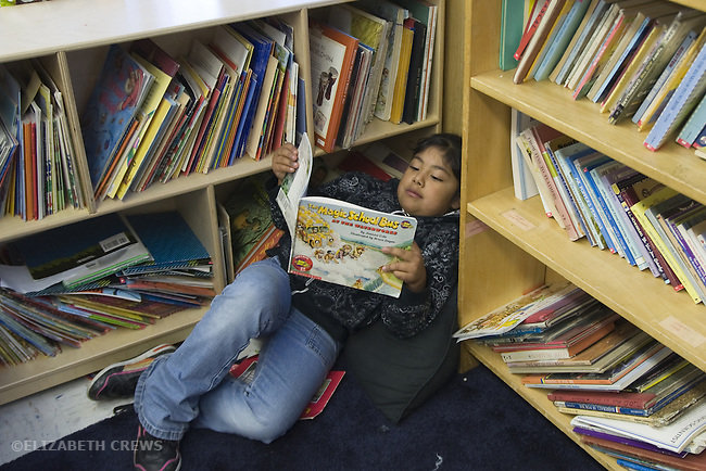 Oakland CA  Latina girl 2nd grader reading book in classroom reading corner
