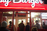 People crowd around the outside take-out window at Tasty Burger on Boylston Street in the Fenway neighborhood of Boston, Massachusetts, USA, in the early hours of Saturday, Dec. 5, 2015.