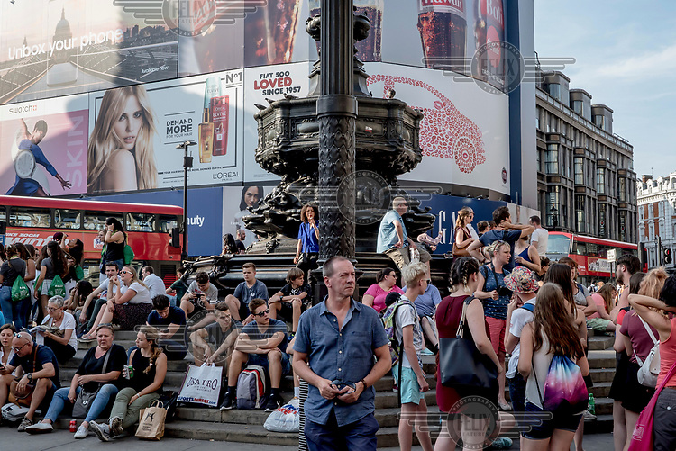 Tourists and shoppers gather at the base of the Eros statue in Picadilly Circus.