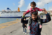 Pictured: A father caries his young daughter on his shoulders after having just arrived to Piraeus port, Greece Sunday 28 February 2016<br /> Re: Hundreds of migrants have arrived from the Greek islands to Piraeus Port, Greece