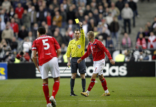 26 March 2008: England midfielder David Beckham, making his 100th appearance for England, is booked by German referee Florian Meyer during the International Friendly game between France and England, played at Stade de France, Paris. France won the game 1-0. Photo: Neil Tingle/Actionplus....080326 football soccer player yellow card