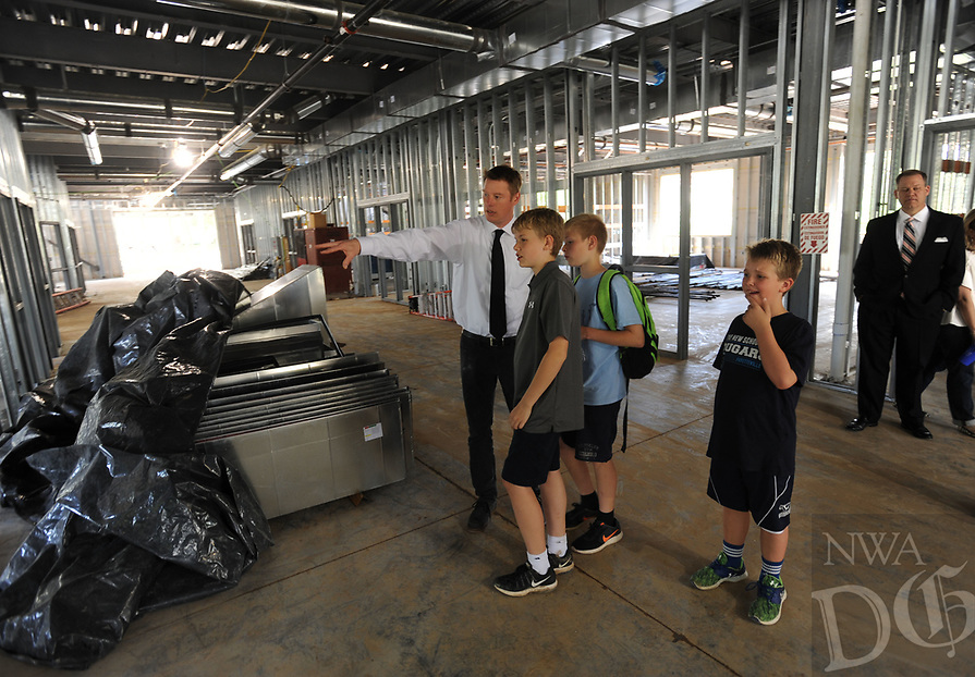 NWA Democrat-Gazette/ANDY SHUPE<br /> Phil Schwartz (left), head of the Upper School at The New School, leads a tour Wednesday, April 19, 2017, for a group of students in the school's Innovation Center during a beam raising and tour of the school's expansion project in Fayetteville. The New School hopes to open the facility in the fall for the 2017-18 school year.