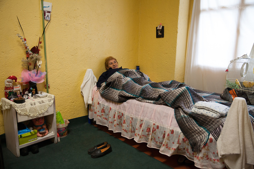 Gloria, a resident of Casa Xochiquetzal, rests in her bedroom at the shelter in Mexico City, Mexico on October 23, 2013. Casa Xochiquetzal is a shelter for elderly sex workers in Mexico City. It gives the women refuge, food, health services, a space to learn about their human rights and courses to help them rediscover their self-confidence and deal with traumatic aspects of their lives. Casa Xochiquetzal provides a space to age with dignity for a group of vulnerable women who are often invisible to society at large. It is the only such shelter existing in Latin America. Photo by Bénédicte Desrus