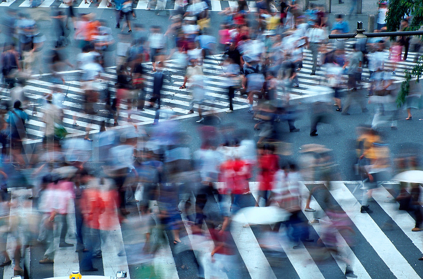 Aerial, blurred motion image of Japanese pedestrians at a busy city intersection. Tokyo, Shibuya district, Japan.