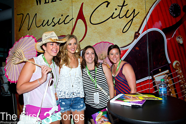 Sarah Darling poses for photos with fans during Day 1 of the 2013 CMA Music Festival in Nashville, Tennessee.