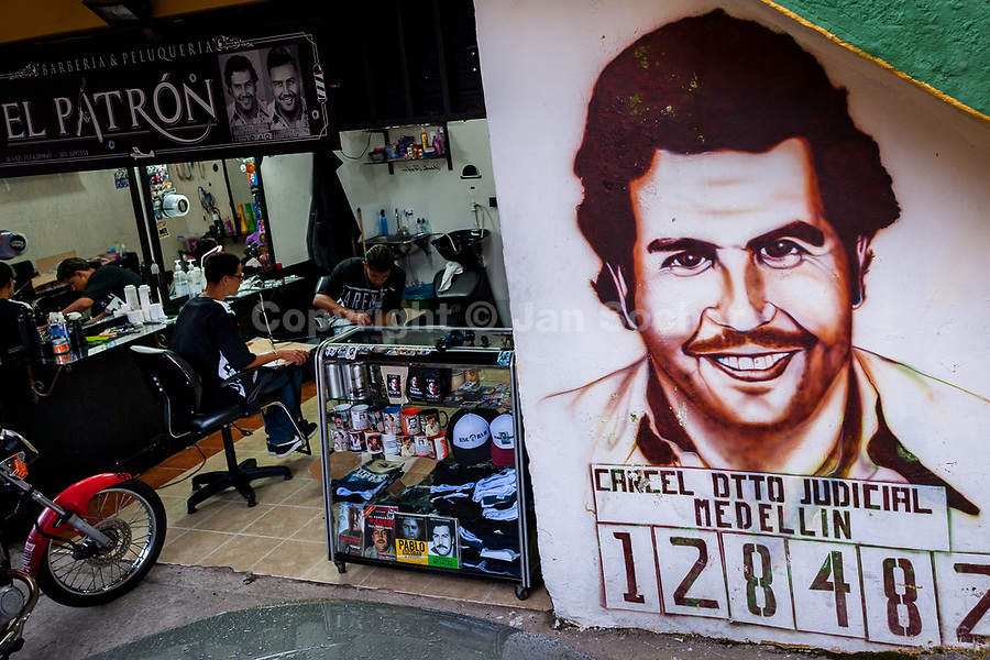 """A portrait artwork, depicting the drug lord Pablo Escobar, is seen painted on the wall next to a barber shop in the Pablo Escobar neighborhood in Medellín, Colombia, 30 November 2017. Twenty five years after Pablo Escobar's death, the legacy of the Medellín Cartel leader is alive and flourishing. Although many Colombians who lived through the decades of drug wars, assassinations, kidnappings, reject Pablo Escobar's cult and his celebrity status, there is a significant number of Colombians who admire him, worshipping the questionable """"Robin Hood"""" image he had. Moreover, in the recent years, the popular """"Narcos"""" TV series has inspired thousands of tourists to visit Medellín, creating a booming business for many but causing a controversial rise of narco-tourism."""