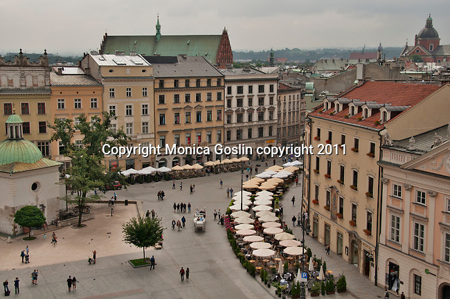 The Main Market Square in Krakow, Poland as seen from the top of the Town Hall Tower with a view of the 11th century Church of St. Adalbert (or St. Wojciech) to the left. The Main Market Square in Krakow, Poland is the largest medieval square in Europe and dates back to the 13th century