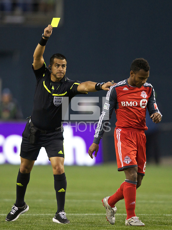 Referee Ricardo Salazar issues a yellow card to Toronto FC midfielder Julian de Guzman during play against the Seattle Sounders at Qwest Field in Seattle Saturday April 30, 2011. The Sounders won the game 3-0.