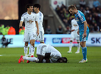 SWANSEA, WALES - FEBRUARY 07: Bafetimbi Gomis of Swansea lies on the ground injured, while Sebastian Larsson of Sunderland (R) is standing above him protesting that he dove during the Premier League match between Swansea City and Sunderland AFC at Liberty Stadium on February 7, 2015 in Swansea, Wales.