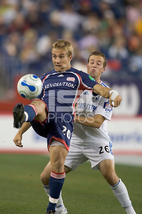 Taylor Twellman (NE Revolution, blue) passes the ball back as Ryan Raybould (KC Wizards, white) defends. NE Revolution tied KC Wizards, 1-1, at Gillette Stadium.