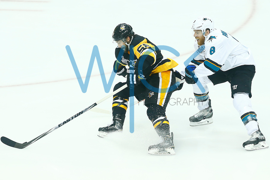 Kris Letang #58 of the Pittsburgh Penguins skates with the puck around Joe Pavelski #8 of the San Jose Sharks in the third period during game one of the Stanley Cup Final at Consol Energy Center in Pittsburgh, Pennslyvania on May 30, 2016. (Photo by Jared Wickerham / DKPS)
