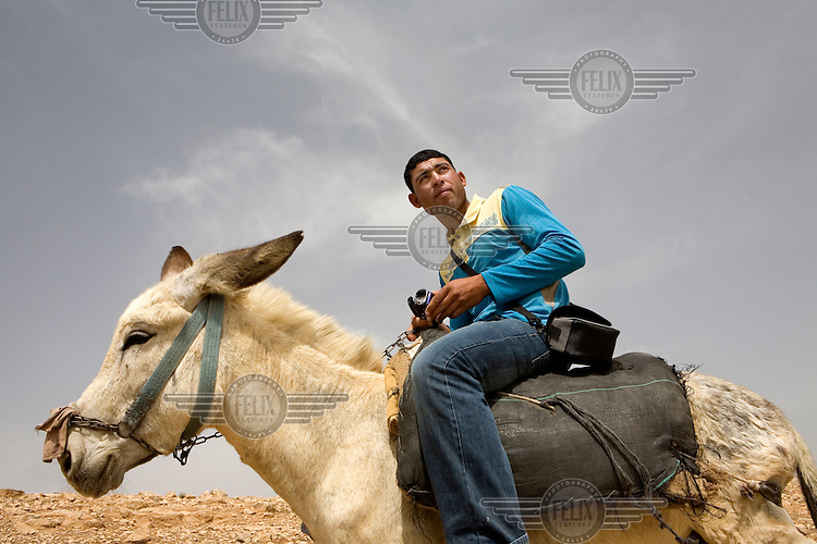 Sheperd Ahmed Omar Mohammed Jundya, astride his donkey with video camera in hand. He is a video volunteer who films his daily life with a camera given to him by Israeli human rights group B?Tselem. In 2010 Ahmad was shepherding with his cousin near his home, when a settler arrived with a gun. After threatening Ahmad and his cousin and claiming they were illegally on his land, he took one of Ahmad?s sheep away (which Ahmad filmed). Later the police looked at the footage and forced the settler to return the animal.