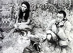 Korean comfort woman found in a hole in the ground by a Chinese soldier. The soldier is discussing the treatment on the phone. (Photo by Kingendai/AFLO)