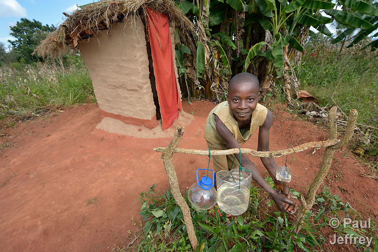 A young woman uses a hand-washing station outside a latrine in Kasangari Ngulube, Malawi. With support from the Ekwendeni Hospital AIDS Program, villagers here participate in a Building Sustainable Livelihoods program, working together to earn and save money, raise more nutritious food, receive vocational training, and promote better hygiene and health awareness.