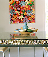 The ceramic serving dishes on the glass tabletop reflect the tones of the vivid painting displayed behind