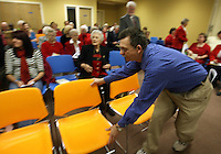 Duane Garrett adds a row of chairs to accomodate the growing crowd at the Saluda Baptist Association offices where the congregation of Mountain Creek Baptist Church met for their first Sunday service after their 165-year-old building was destroyed by a fire earlier in the week.