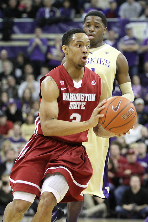 Reggie Moore, Washington State sophomore point guard, prepares to dish the basketball to a teammate during the Cougars 80-69 road victory over arch-rival Washington at the Alaska Airlines Arena in Seattle, Washington, on February 27, 2011.  With the victory, Moore and the Cougars swept the regular season series from the Huskies, two games to none.