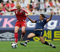 USWNT midfielder (7) Shannon Boxx slides into Canada's (4) Clare Rustad during the finals of the Peace Queen Cup.  The USWNT defeated Canada, 1-0, at Suwon World Cup Stadium in Suwon, South Korea.