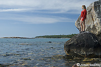 Young girl standing on a rock on the lakeshore
