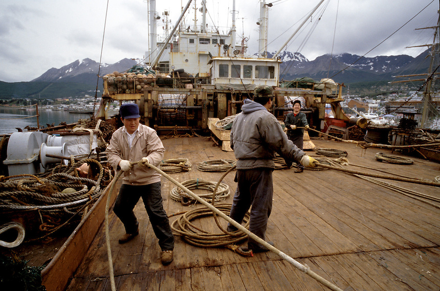 "Asian crew members aboard the Argentine-registered Tai-An factory trawler prepare the ship to embark from Ushuaia on a several-month tour of the South Atlantic. Capt. Beto Tagliamonte didn't expect the voyage to tax the ship's capacity to haul in 5,000 tons of uncleaned fish per trip. ""There's just not that many fish out there,"" he said."