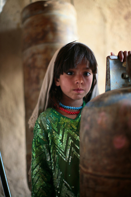 A girl stands next to a propane cylinder as her father talks to U.S. Marines from Company L, 3rd Battalion, 6th Marine Regiment in his shop near Marjah, Afghanistan. March 10, 2010 DREW BROWN/STARS AND STRIPES