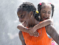 Waterbury, Conn. 30 July 06: Irazjah Richardson, 12, carries her screaming cousin Kourtne Johnson, 5, through the sprinkler at Chase Park...Josalee Thrift Photo