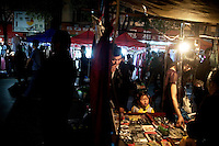 Shoppers look at a stall in a street market in Shaoxing, Zhejiang Province, China.
