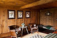 Three vintage mountaineering photographs are displayed on the wood-panelled wall of this bedroom